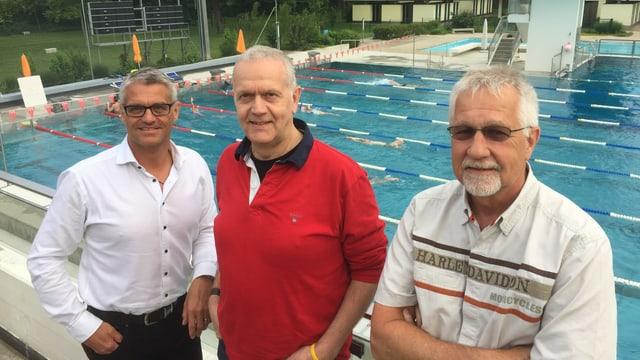 Drei Männer stehen vor einem Schwimmbecken