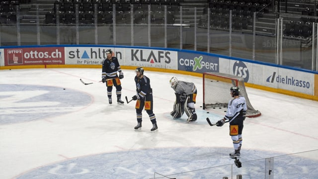 Eishockeyfeld mit vier Spielern beim Training.