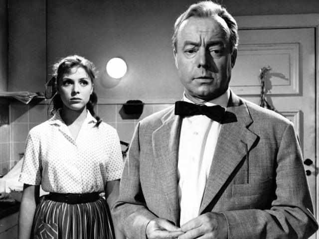 Ein Schauspieler schaut besorgt. Eine Frau im Hintergrund ebenfalls. Schwarz-weiss Aufnahme.