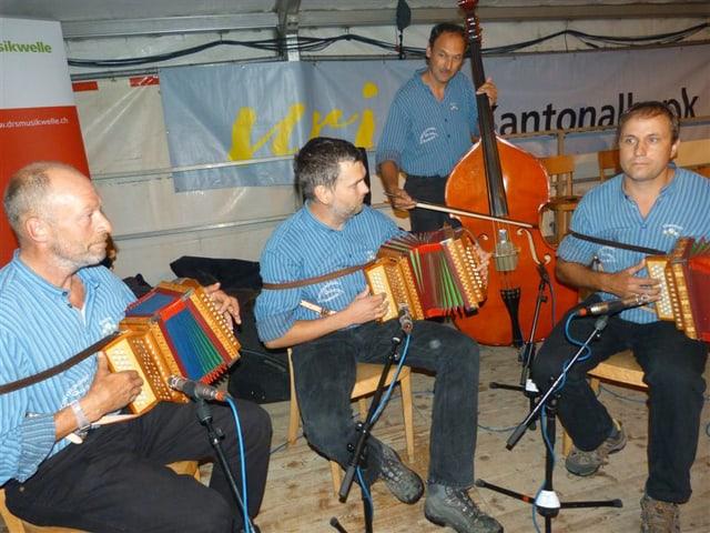 Drei Schwyzerörgeler und ein Bassgeiger während eines Auftritts auf einer Zeltbühne.