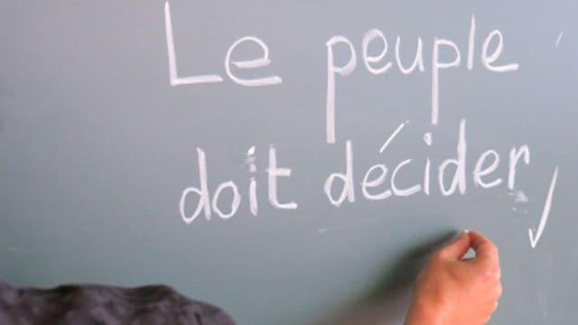 An Wandtafel wird geschrieben: Das Volk muss entscheiden.