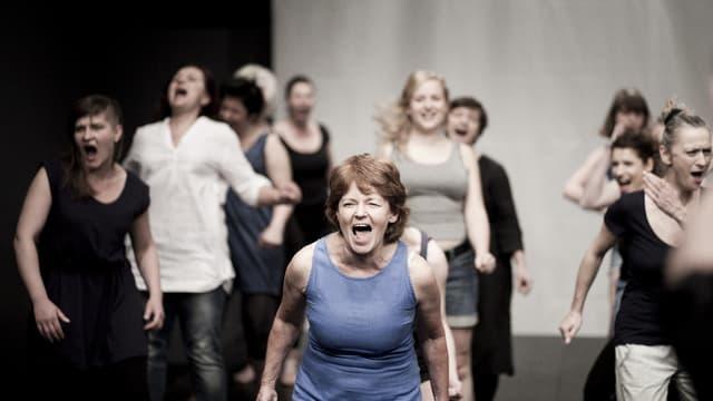 Die Sängerinnen eines Chors auf einer Bühne, in Bewegung und mit offenen Mündern.