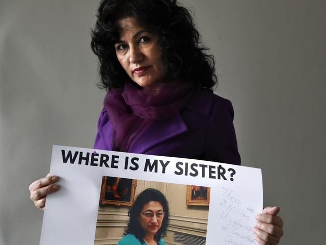 Uigurische Exilantin mit Bild ihrer Schwester, die möglicherweise in einem Internierungslager verschwunden ist.