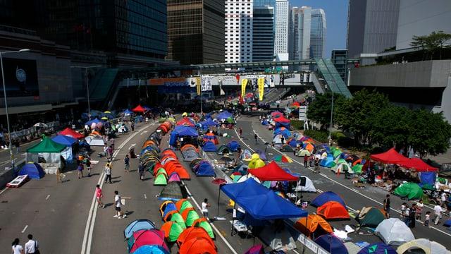 Zelte auf einer mehrspurigen Strasse in Hongkong, im Hintergrund Hochhäuser