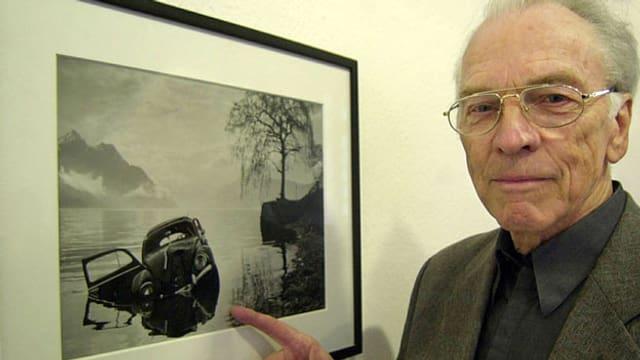 Arnold Odermatt steht neben einer Wand, an der Wand hängt ein schwarzweiss Bild eines kaputten Autos.