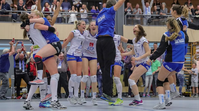 Volleyballspielerinnen in weissen und blauen Trikots feiern den Sieg.
