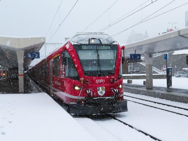 Schneefall vor rotem Zug