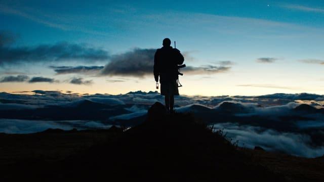 Ein Junge steht oben auf einem Berg.