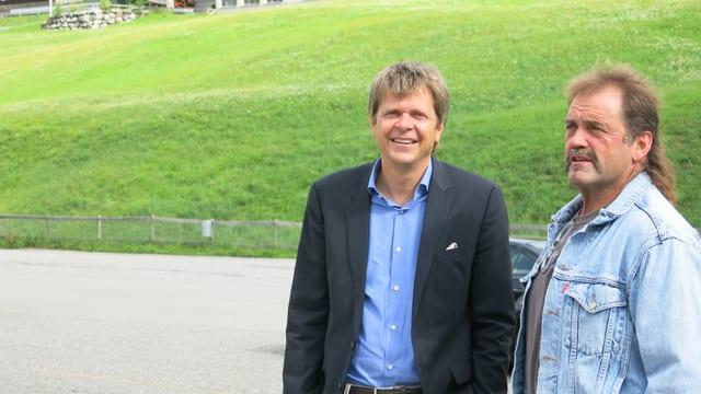 Zwei Männer stehen auf einem Parkplatz, im Hintergrund eine grüne Wiese.