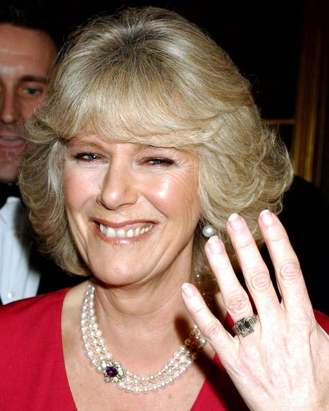 Camilla Parker Bowles zeigt lachen ihre linke Hand mit Diamantring.