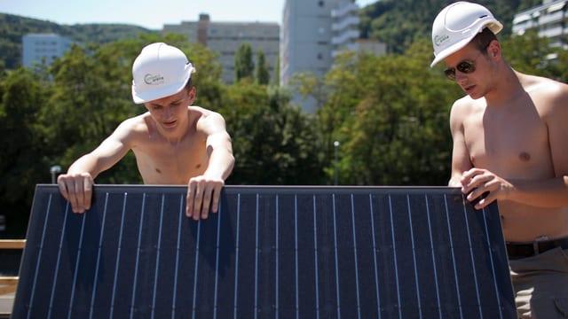 Lehrlinge montieren Solarzellen auf einem Dach.