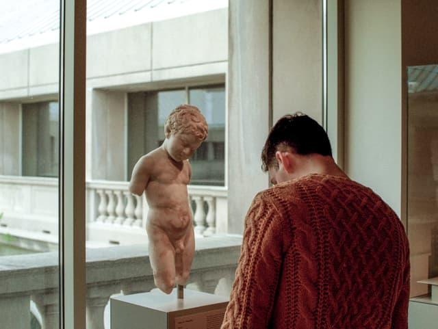 Ein Mann in orangem Pulli steht vor der Statue eines nackten Knaben und liest die Texttafel.