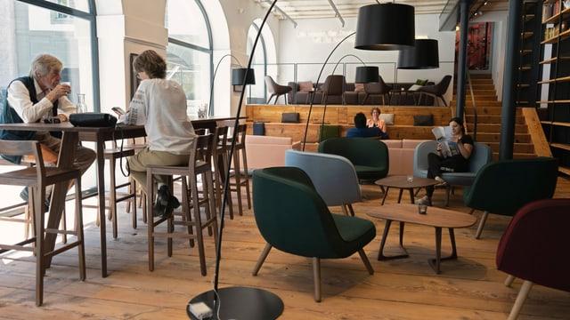 Bartische und Sessel in einem Raum mit breiten Holzbrettern am Boden