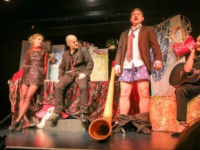 Zwei Festbrüder und eine Dame vergnügen sich an einem Fest. Ein mann steht mit Krawatte, Kittel und in den Unterhosen da.