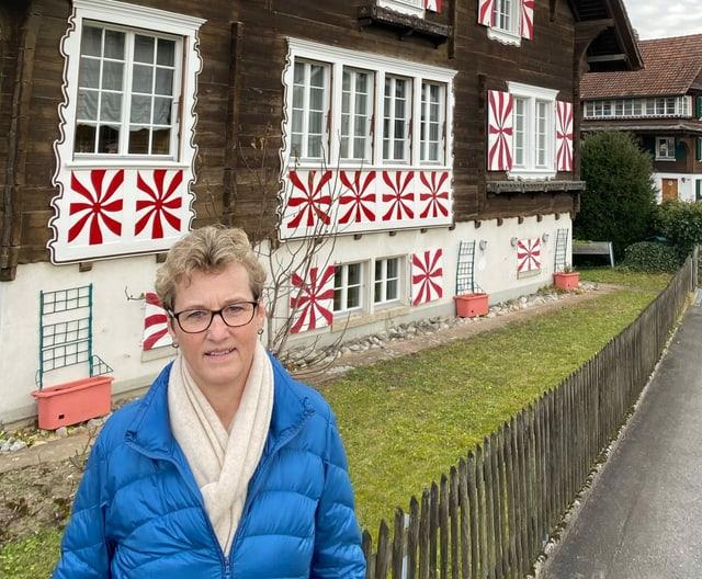 Frau in kobaltblauer Stepjacke steht vor Bauernhaus.