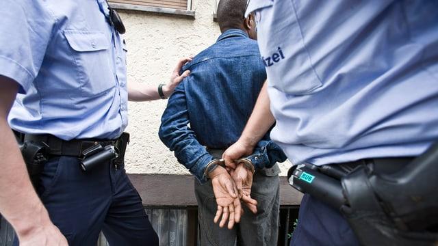 Zwei Beamte hinter einem dunkelhäutigen Mann in Handschellen.