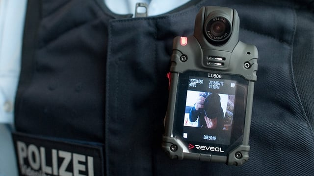 Ein Polizist trägt eine Kamera an seiner Uniform.