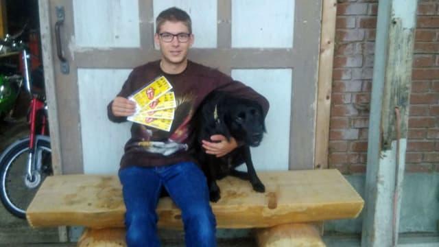 Junger Mann hält seinen Hund und vier Rolling-Stones-Tickets.