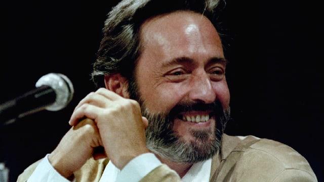 Helmut Dietl lacht. Neben ihm ist ein Mikrofon.