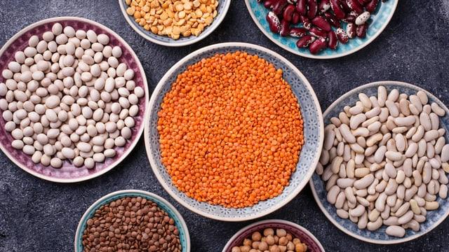 Verschiedene Hülsenfrüchte in grossen und kleineren Schalen.