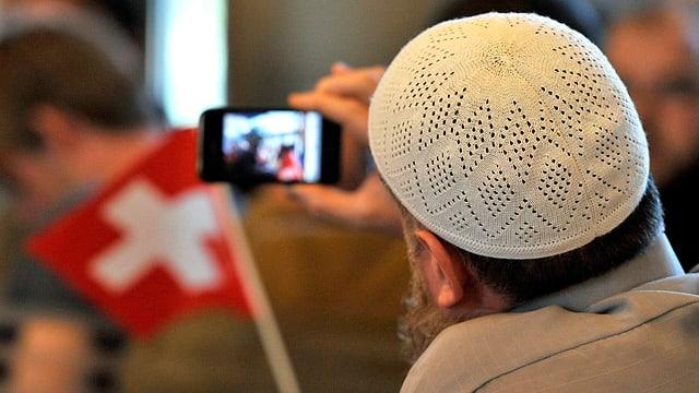 Ein Muslime fotografiert eine Demonstration der Vereinigung Islamische Jugend Schweiz. Ein Demonstrat trägt eine Schweizer Fahne. (keystone)