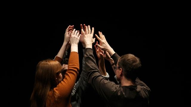 Fünf Leute heben im Kreis die Hände und bilden ein Menschenzelt.