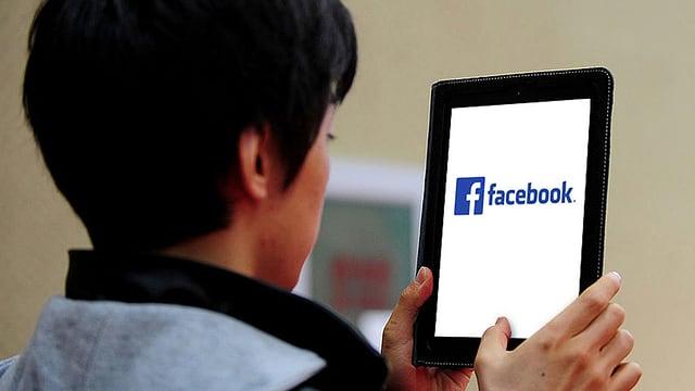 Mann hält Tablet in der Hand. Auf dem Bildschirm das Facebook-Logo.