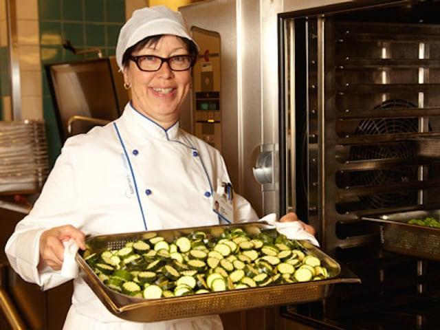 Frau in Kochbekleidung mit einem Ofenblech voll geschnittener Zucchini in der Hand