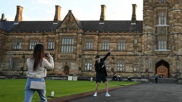 Zwei Studenten fotografieren sich vor der Uni von Sydey.