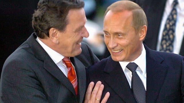 Gerhard Schröder umarmt lächelnden Wladimir Putin
