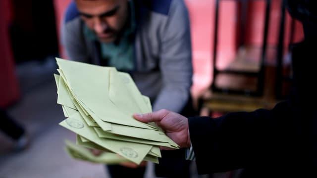 Eine Hand hält grünliche Abstimmungscouvert im Hintergrund ein Mann der sich bückt
