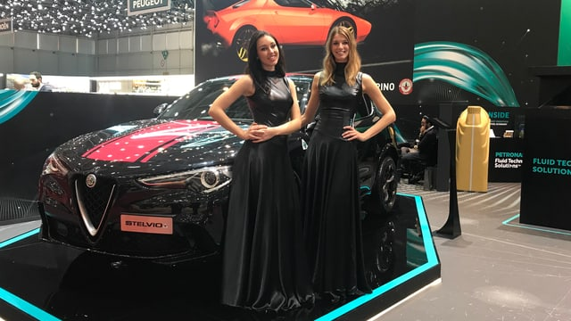 Zwei Frauen in langen Abendkleidern posieren vor einem Auto.