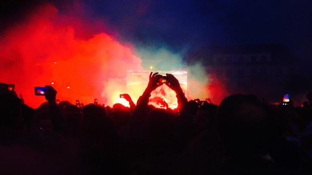 Fans vor Grossleinwand in farbigen Rauch gehüllt