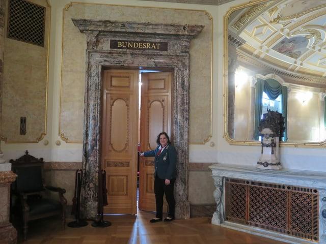 Frau steht vor grosser Tür.