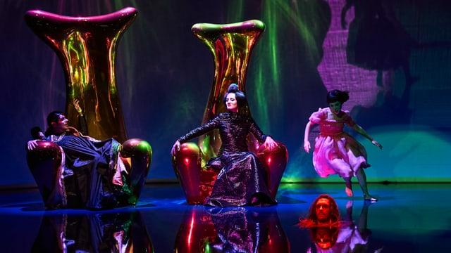 Mehrere Darsteller auf einer Bühne. Zwei davon sitzen auf riesigen goldenen Thronen.