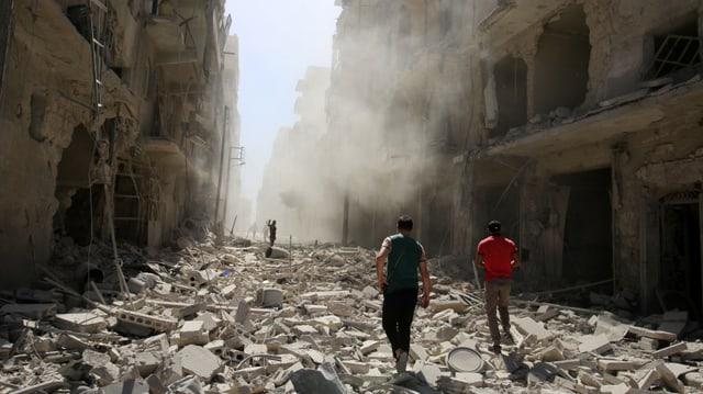 Häuserschlucht in Aleppo mit der Trümmerübersähten Strasse dazwischen und zwei Menschen darin