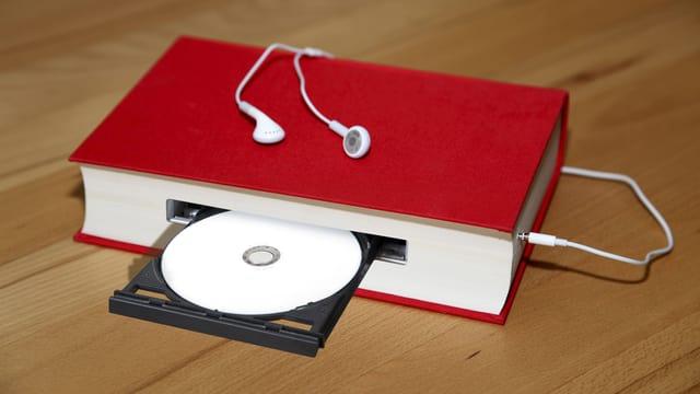 Ein rotes Buch, das gleichzeitig ein CD-Laufwerk ist, daran angeschlossen ein Kopfhörer.