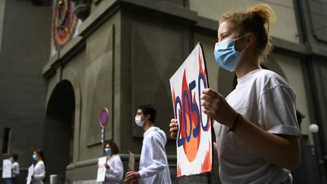 Jugendliche mit Schutzmaske halten Plakate.