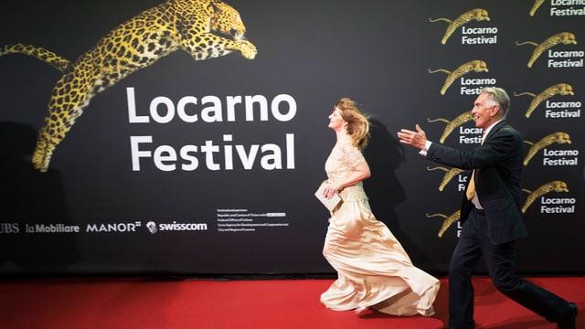 """eine Frau in Abendkleid und ein Mann in Anzug rennen über den roten Teppich. Im Hintergund eine schwarze Wand, auf der gross der Schriftzug """"Locarno Festival"""" und ein springender Leopard zu sehen sind."""