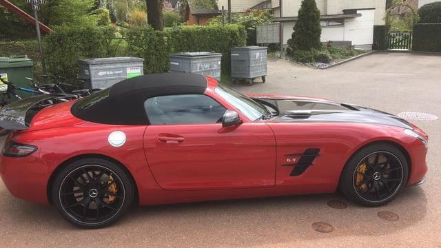 Ein roter Sportwagen mit schwarzem Dach.