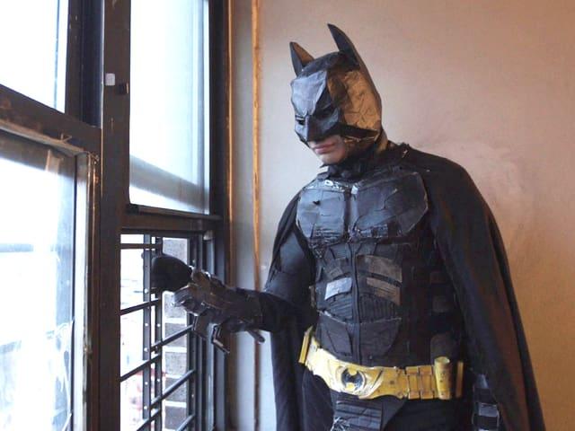 Eine verkleidete Batman-Figur am Fenster, hinausschauend.