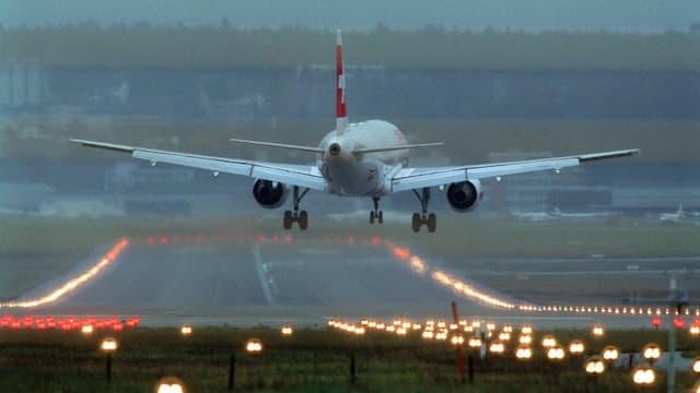 Ein Flugzeugt der Swiss landet in der Dämmerung auf der befeuerten Piste