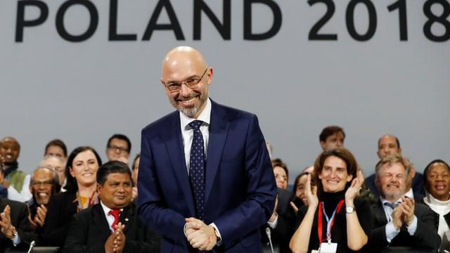 Ein Mann steht lächelnd auf der Bühne.