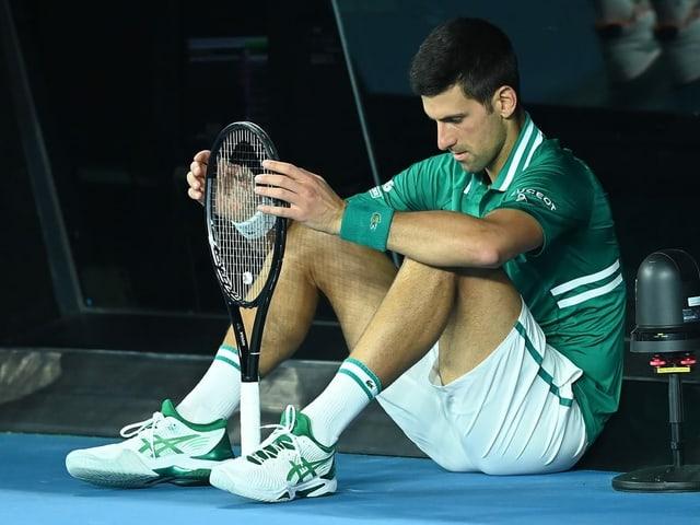 Novak Djokovic sitzt am Boden