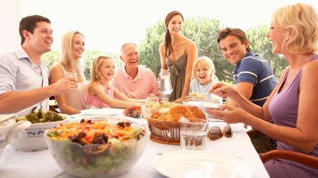 Eine Familie sitzt fröhlich am Tisch und isst.