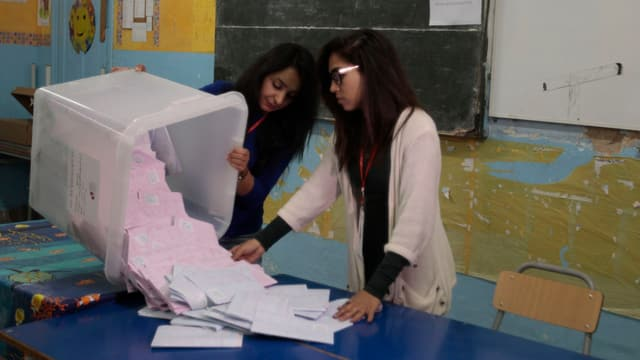 Wahlhelferinnen leeren eine Box mit Stimmzetteln.