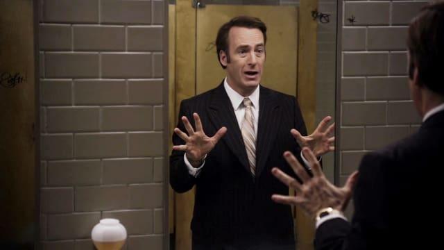 Anwalt Saul Goodman vor Spiegel mit ausgebreiteten Armen und Händen.