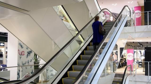 Eine einzelne Person auf einer Rolltreppe in einem Geschäft.