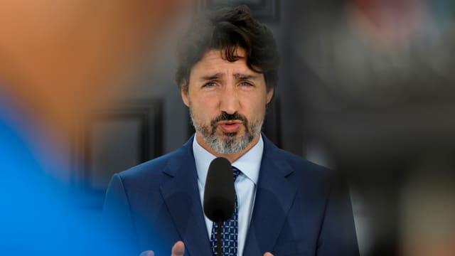 Trudeau (mit Bart) spricht in ein Mikrofon.