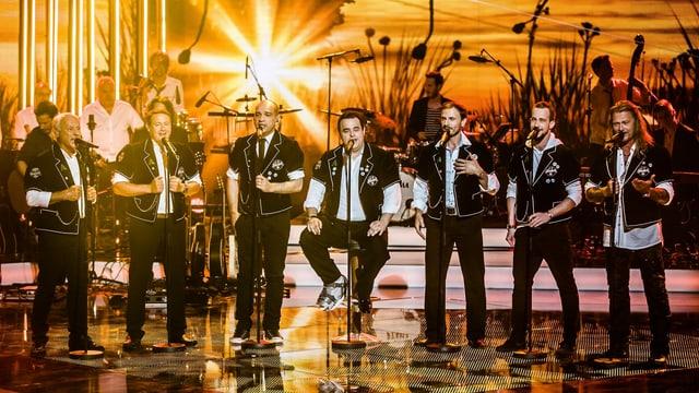 7 Männer aufgereiht nebeneinander während eines Fernseh-Auftritts